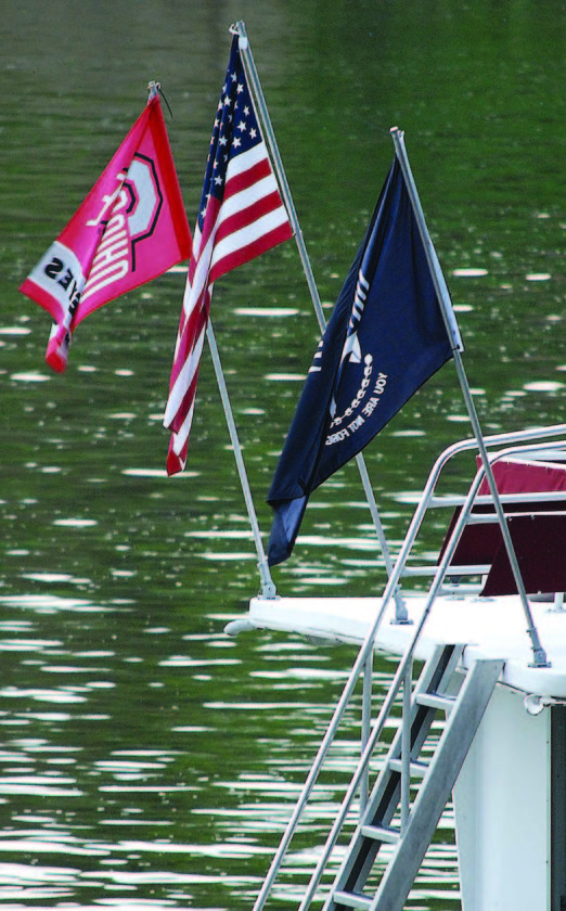 Flags line the stern of a houseboat on the Muskingum River.
