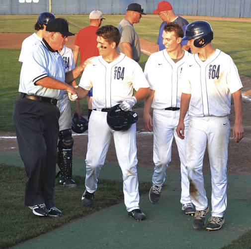 Marietta Post 64's Clay Hayes is congratulated by the umpire after the Marietta American Legion baseball team mercied Hebron Post 285, 12-2, in 8 innings at Don Schaly Stadium Friday night. Photo by Ron Johnston.