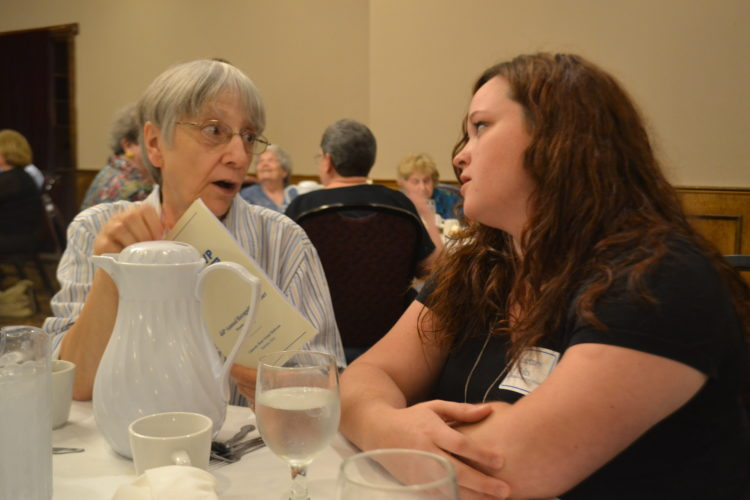 PEYTON NEELY   The Marietta Times Carolyn Miller with Senior Wheels Transportation looks over the program with Courtney Folts, direct care specialist from WASCO, at the 44th annual RSVP Recognition Dinner.