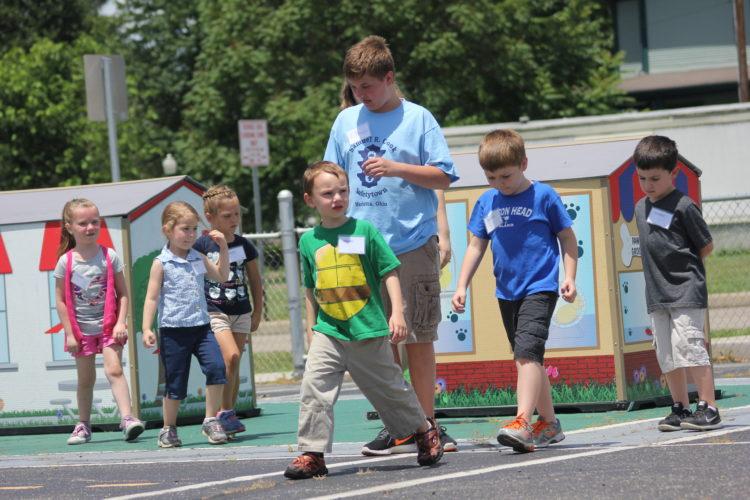JANELLE PATTERSON   The Marietta Times Landon Dunn, 5, of Marietta, looks both ways while crossing a miniature street at Safetytown Monday.