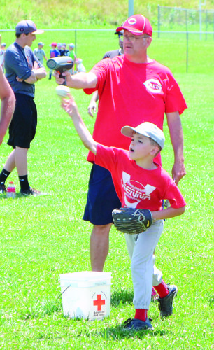 JORDAN HOLLAND The Marietta Times Reds Legends clinic director Mike Wagner tests the pitching speed of youngsters during a drill Tuesday at Jackson Park in Vienna.