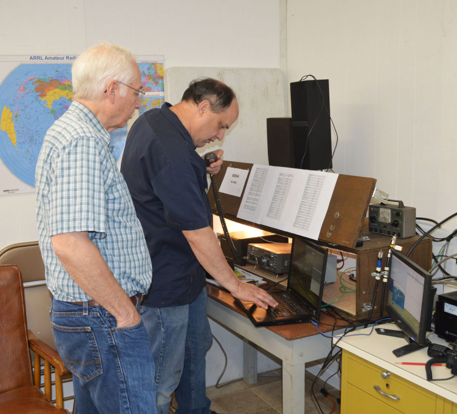 DOUG LOYER  Special to the Times Richard Miller, left, president of the Marietta Amateur Radio Club watches club member Matt Pooler making contact with another station.