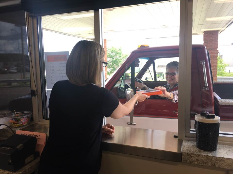 PEYTON NEELY   The Marietta Times Melissa Reed, librarian assistant, hands Marietta resident Sara Beaver, 65, her book through the drive-thru location of the Washington County Public Library on Tuesday.