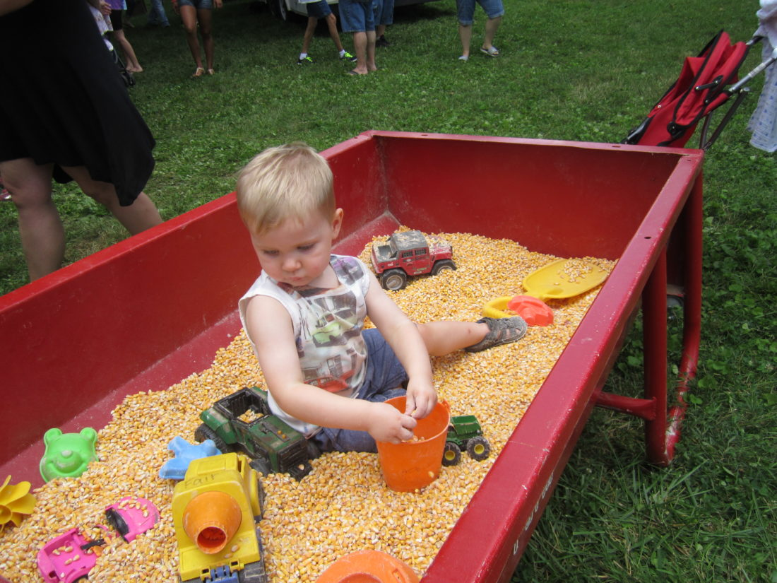 WAYNE TOWNER  Special to the Times Sebastian Skinner, 2, of Marietta, played in a sandbox filled with corn kernels Saturday during the Marietta Sweet Corn Festival.