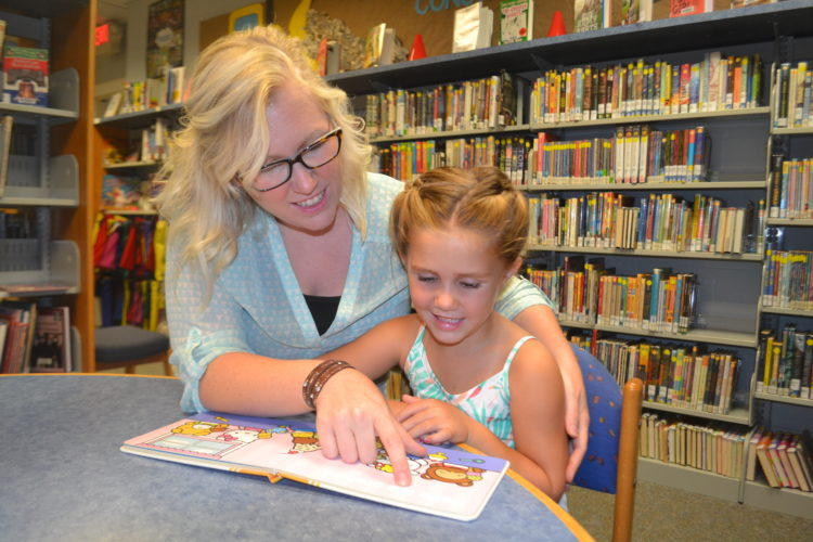 PEYTON NEELY   The Marietta Times Waterford residents Jesse Townsend, 31, and her daughter Chloee Townsend, 5, read a book together at the Beverly branch of the Washington County Library on Wednesday afternoon.