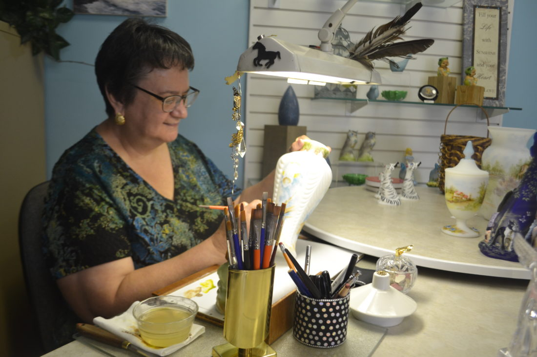 PEYTON NEELY   The Marietta Times Robin Spindler, decorator and designer, paints a design onto a piece of Fenton glass at her workspace in the new Fenton Gift Shop located in Boaz, W.Va.