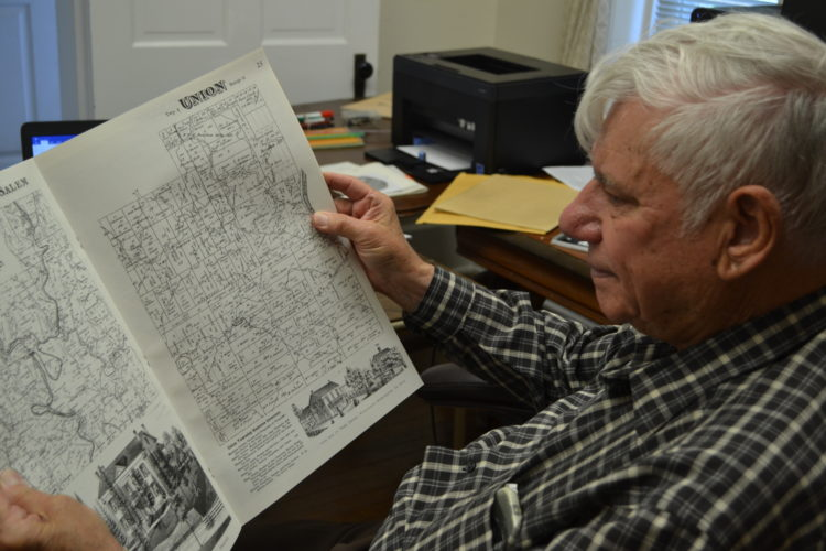 KATE YORK   The Marietta Times Gus Letto looks through the 1875 Atlas of Washington County on Tuesday. Letto has been researching Churchtown and its people for nearly 60 years.