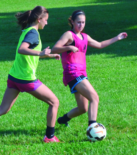 RON JOHNSTON The Marietta Times Marietta High's Lexie Mullen, right, battles teammate Paige Hartley, left, for the ball during a practice drill last week in Devola.
