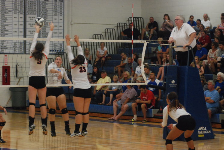 JORDAN HOLLAND The Marietta Times Warren's Emily Jackson, center, attempts a spike during a high school volleyball match against Marietta last season in Vincent.