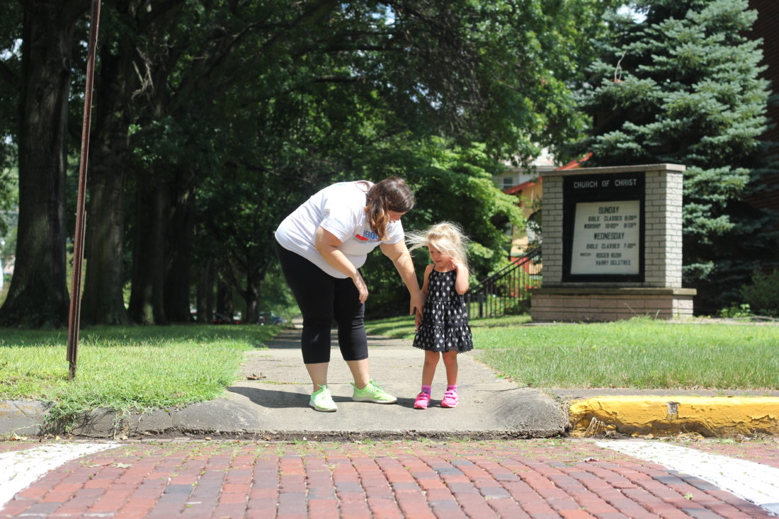 JANELLE PATTERSON   The Marietta Times Danielle Allphin, 33, comforts her daughter Gabrielle, 3, after she trips on the way to the park.