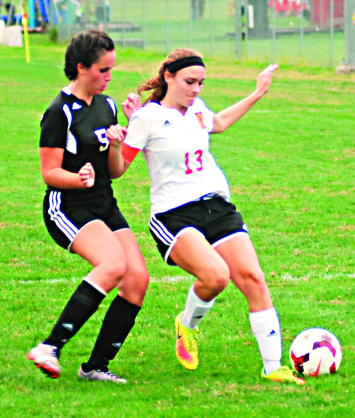 Marietta's Grace Crosby (13) controls the ball as New Philadelphia's Cara Ramey defends during a high school girls soccer match Tuesday at Jerry Brock Field in Devola. Marietta won, 4-0.  JORDAN HOLLAND The  Marietta Times