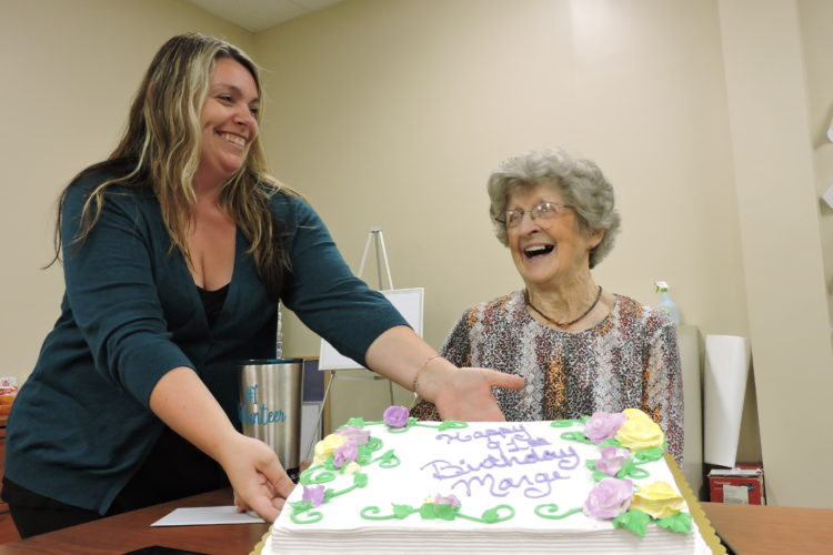 SAM SHAWVER   The Marietta Times Marietta Home Health and Hospice aide Dusty DeLancey, left, helps longtime volunteer Marge Stacy show off her cake during an early birthday celebration at the hospice office Thursday. Stacy turns 91 on Tuesday.
