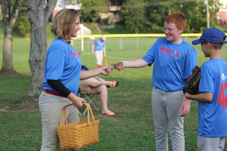 JANELLE PATTERSON   The Marietta Times Hollis Sturgill, 12, of Warren Township, sells baked goods to brothers Ethan,11,  (center) and Jacob Berg, 12, (right) to raise the final dollars in her $2,000 fundraising goal for the Brooks family while at her baseball game in Marietta Monday.