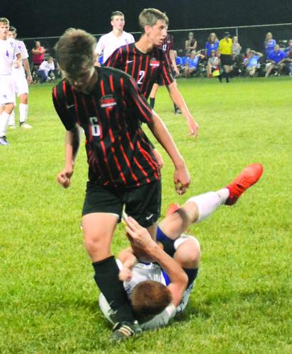Marietta's Sean Fournier (6) battles Warren's Kyler Gardner for the ball during a high school boys soccer match Tuesday in Vincent. Warren won, 4-0.  RON  JOHNSTON The Marietta Times