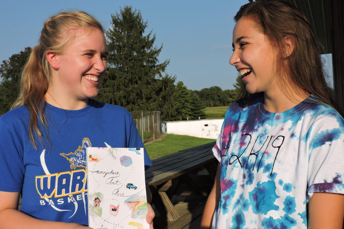 "SAM SHAWVER   The Marietta Times Abby Werry, left, shows her latest book, ""Anywhere But Here,"" to friend Caroline Stollar during a recent Warren High School soccer game."
