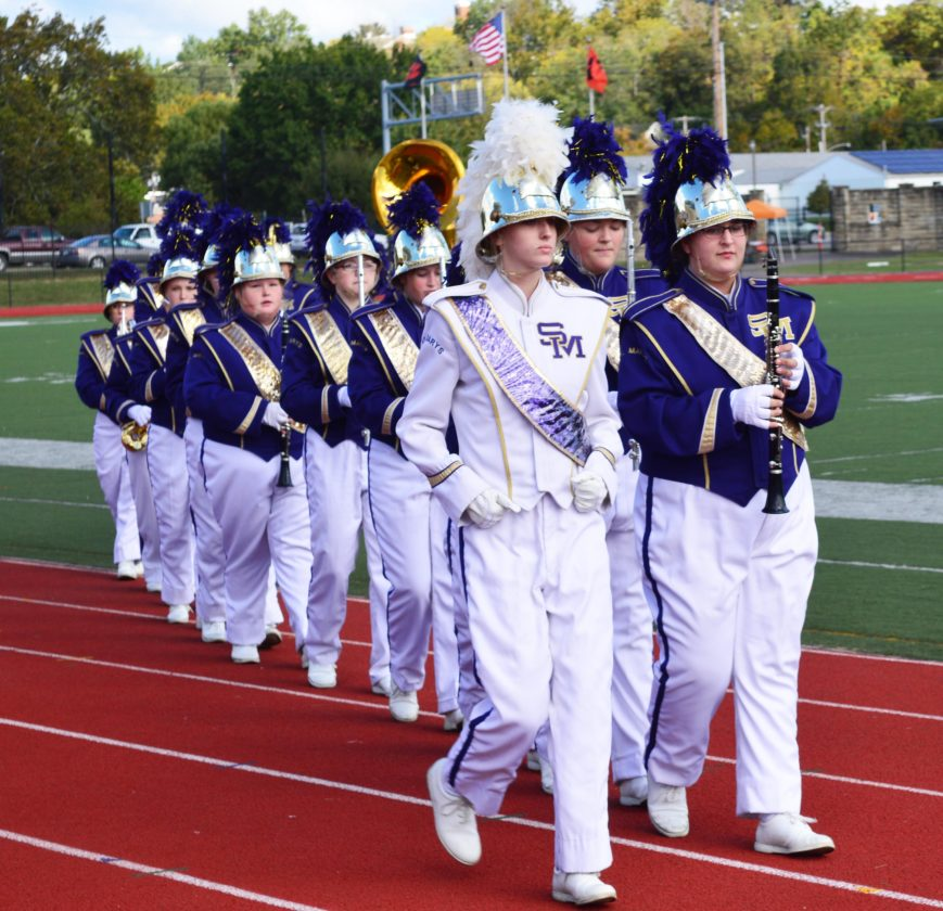 The St. Marys High School Marching Blue Devils come off the field after performing.