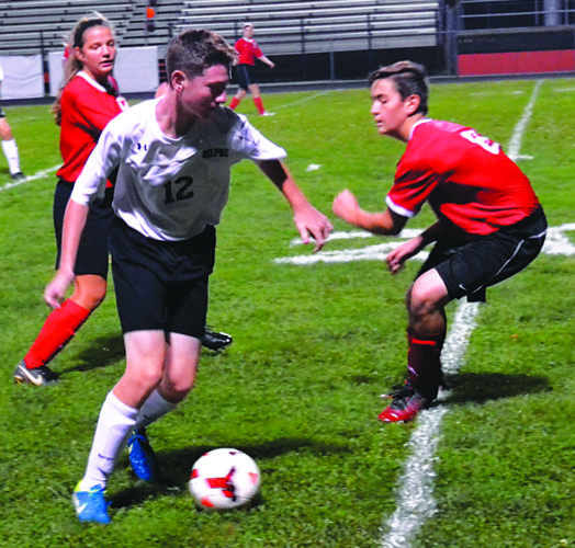 Belpre's Tyce Church (12) makes a move on Caldwell defender Clayton Bettinger during prep soccer action at Ralph Holder Stadium Thursday night. Church had one of Belpre's five goals in a 5-2 triumph. Photo by Ron Johnston.