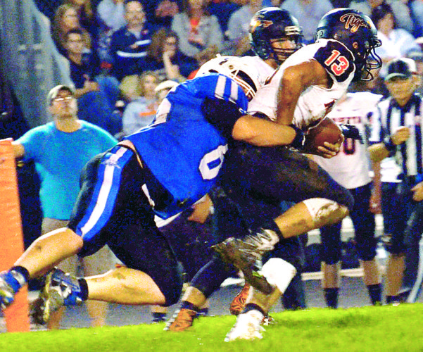Photo courtesy of The Daily Jeffersonian Cambridge High's Garrett Dostall (65) tackles Marietta's Corbin Alkire (13) during Friday night's high school football game at McFarland Stadium.