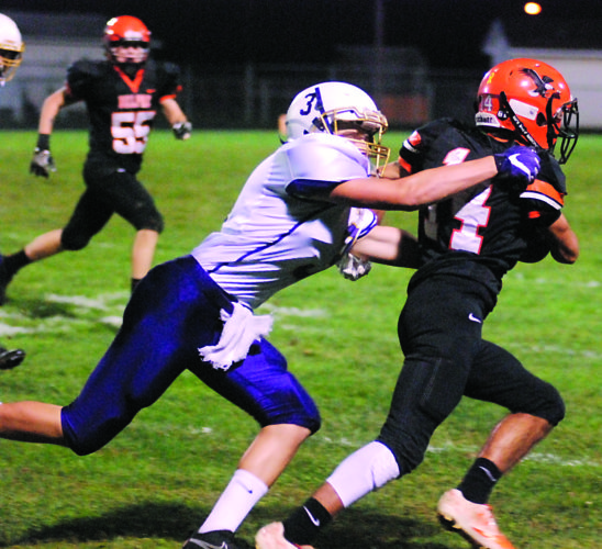 STEVE HEMMELGARN The Marietta Times Belpre's Logan Adams (14) tries to get away from Lucasville Valley's Nate Crabtree during a high school football game Friday night at Ralph Holder Stadium.