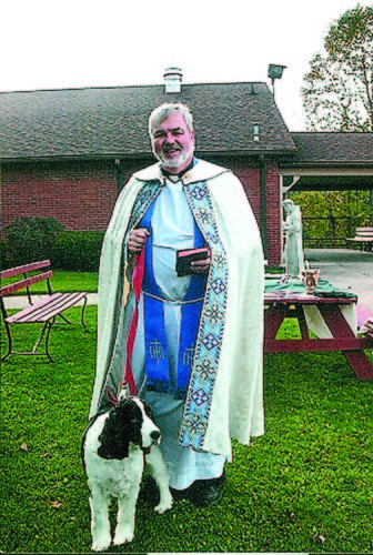 Photo submited by Ron Surella Father Tim Shannon stands with his dog during a previous Blessing of the Animals at Our Lady of Mercy Church in Lowell.