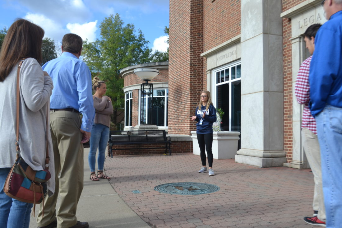 MICHAEL KELLY   The Marietta Times Marietta College ambassador Justice Held explains a myth concerning the college seal in the pavement outside one of the campus buildings to a tour group of prospective students and their families this week. Held said the legend goes that any student who steps on the seal won't finish their degree within four years.