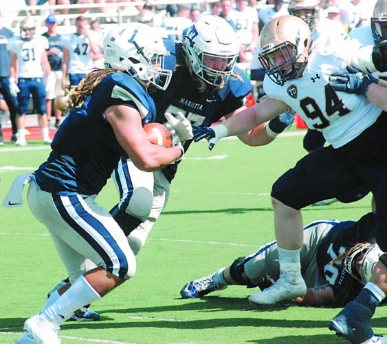 JORDAN HOLLAND The Marietta Times Marietta College's Roger Walker (1) follows the block of teammate Caleb Riggleman during a college football game against John Carroll earlier this season at Don Drumm Stadium.