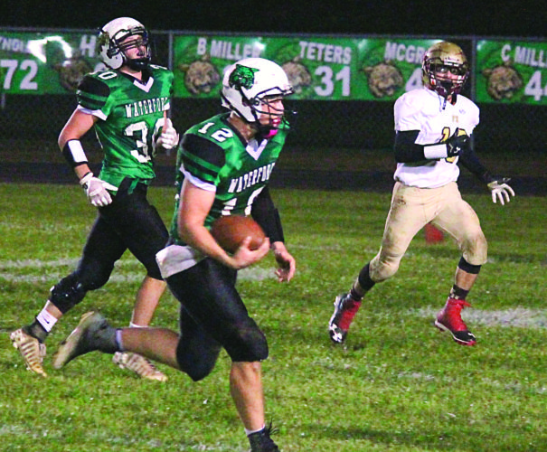 Photo courtesy of Patti Miller Waterford's Peyten Stephens (12) carries the ball as teammate Braden Bellville (30) looks on during a high school football game against Federal Hocking Friday night. Waterford won, 52-8.