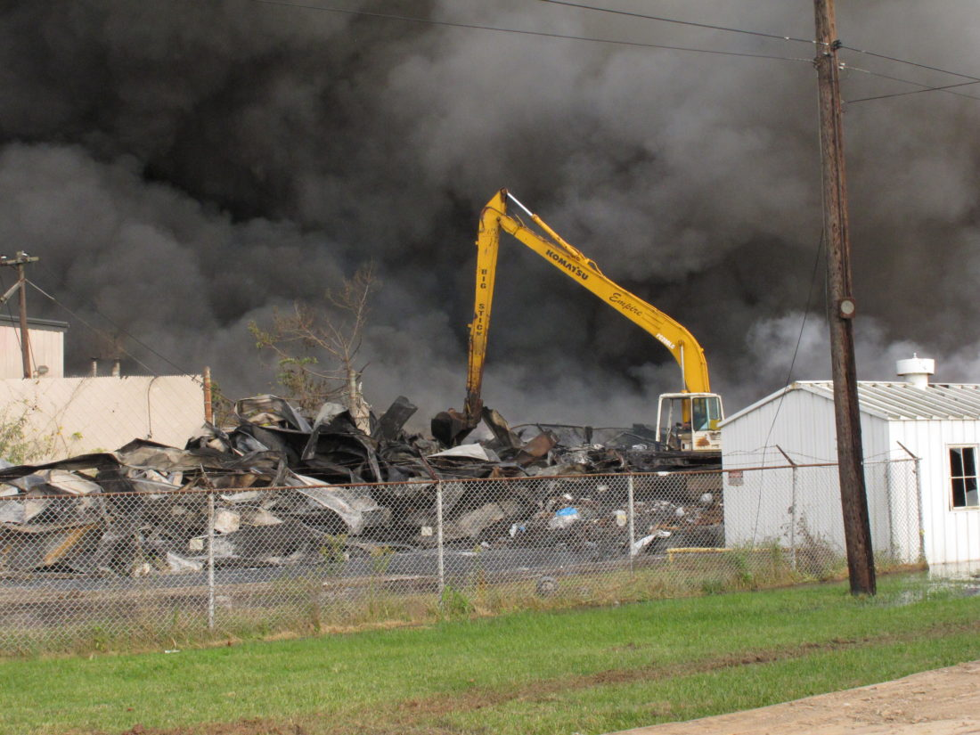 Photo by Jess Mancini. An equipment operator from Empire Builders moves debris Saturday at the former Ames shovel plant in south Parkersburg. The fire that started early Saturday morning destroyed most of the facility where plastics were stored.