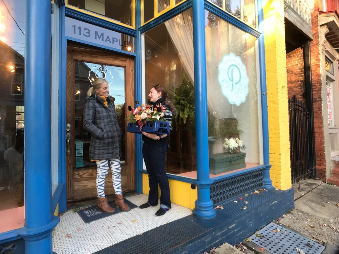 JANELLE PATTERSON   The Marietta Times Caroline Waller, owner of Passiflora Studio, left, and Aurora Held Dodd, of Marietta, discuss flowers Friday in front of Waller's shop in Harmar.