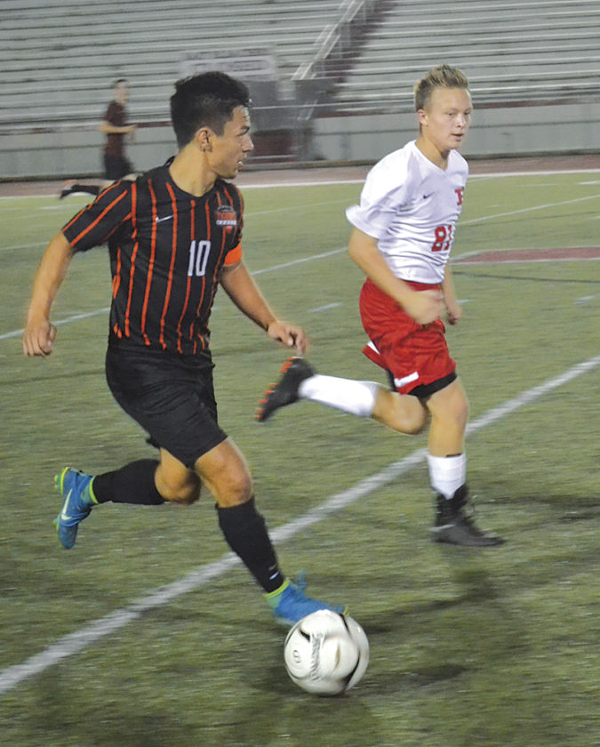 Marietta's Austyn  Chen dribbles past Parkersburg's Caden Rogers during a high school soccer game earlier this season.