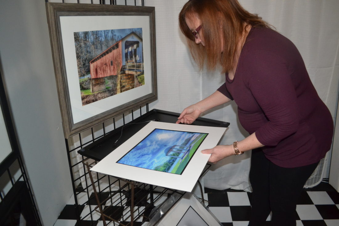 ERIN O'NEILL   The Marietta Times Deb Lorentz, a photographer from the Veto area, places a mat around a photo she took in Parkersburg on Monday. Lorentz will have several of her photos for sale at the Marietta High School Band Boosters craft show Saturday at the fairgrounds.