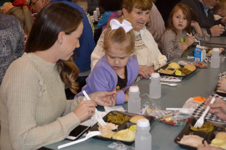 ERIN O'NEILL  The Marietta Times Ashley Whited, left, tries to get her 3-year-old daughter, Evelyn, to try some turkey during the annual Putnam Elementary School Thanksgiving lunch Wednesday.