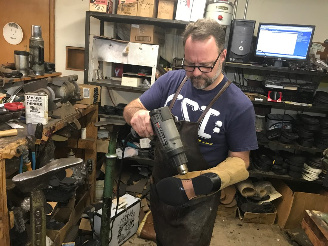 JANELLE PATTERSON   The Marietta Times Bill Gossett, 47, of Marietta, uses a heat gun on a cowboy boot Thursday while in his shop, Cobbler John's, located in the basement of the old Dime Bank building. The heat gun sets the polish on the new welt and sole.