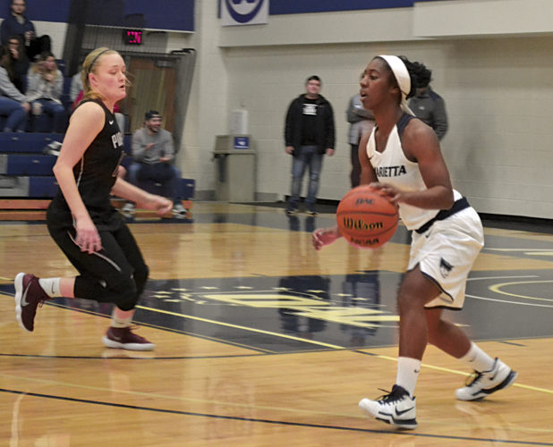 Marietta College's Amisha Herd, right, dribbles upcourt as Transylvania's Celia Kline defends during women's basketball action at Ban Johnson Arena Sunday. MC won 70-67. Photo by Ron Johnston