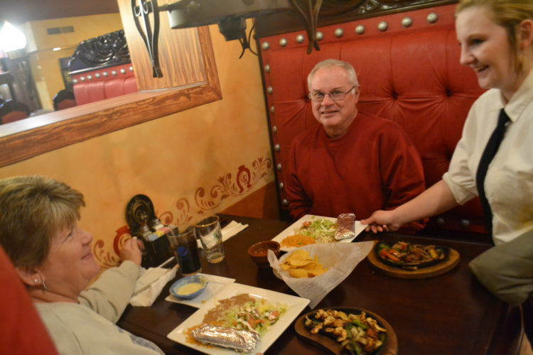 MICHAEL KELLY   The Marietta Times Server Chelsea Morris delivers entrees to Sammie and Tom Sayre of Marietta at the Gran Ranchero restaurant Tuesday. The restaurant opened Nov. 11 in the old Ryan's location on Pike Street.