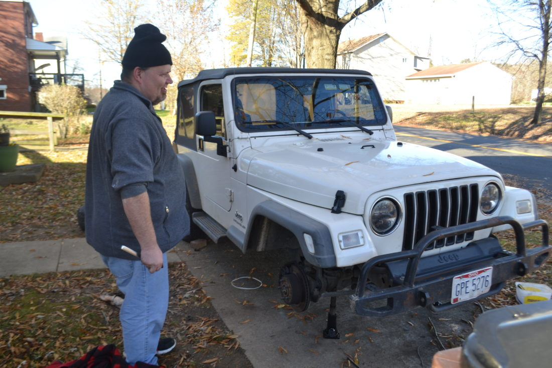 MICHAEL KELLY   The Marietta Times Rodney Lightfrizz works on the brakes of his Jeep at his home on South Sixth Street in Marietta's south side neighborhood. Lightfritz said he has lived in the area all his life and likes it.