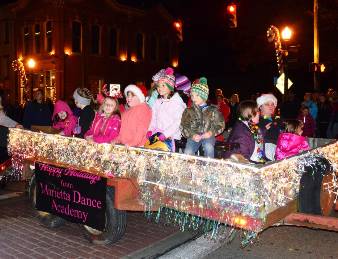 Several kids sit on a float by the Marietta Dance Academy in Saturday evening's parade.