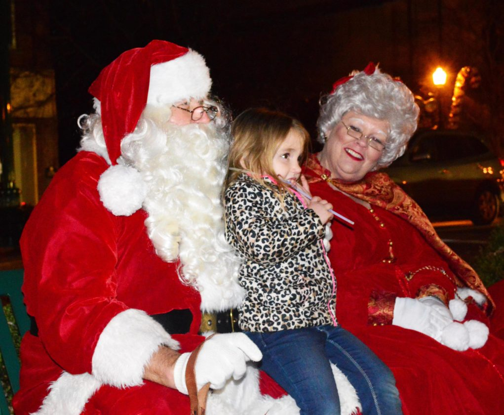 Abigail Friend, 4, of Newport, shares a moment with Santa and Mrs. Claus on the Armory lawn.