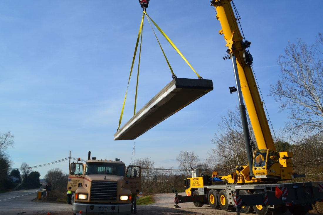 MICHAEL KELLY   The Marietta Times A 225-ton crane from Mustang Aerial Services in Marietta lifts a 16,000-pound concrete slab for placement as part of the new East Bridge on the Devola Multi-Use Trail on the Broughton Nature and Wildlife Education Area Thursday morning.