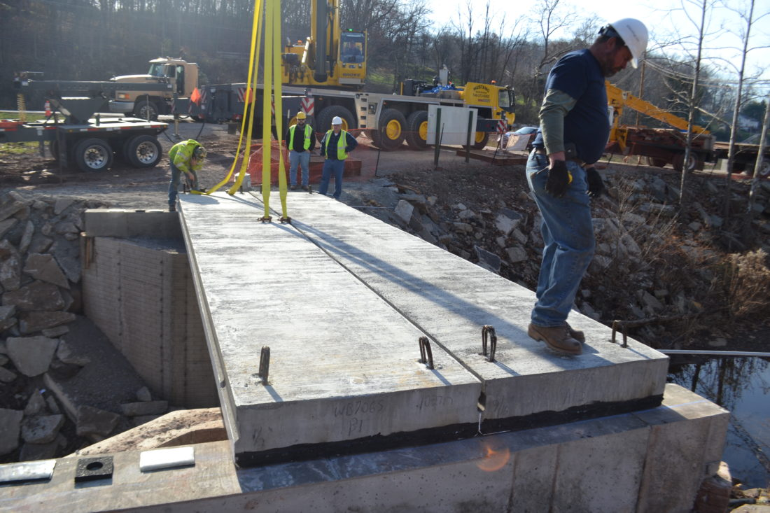 MICHAEL KELLY   The Marietta Times Doug Lowe of Lowe Construction and Excavating checks a freshly positioned concrete slab as crew members work on the new East Bridge of the Devola Multi-Use Trail.