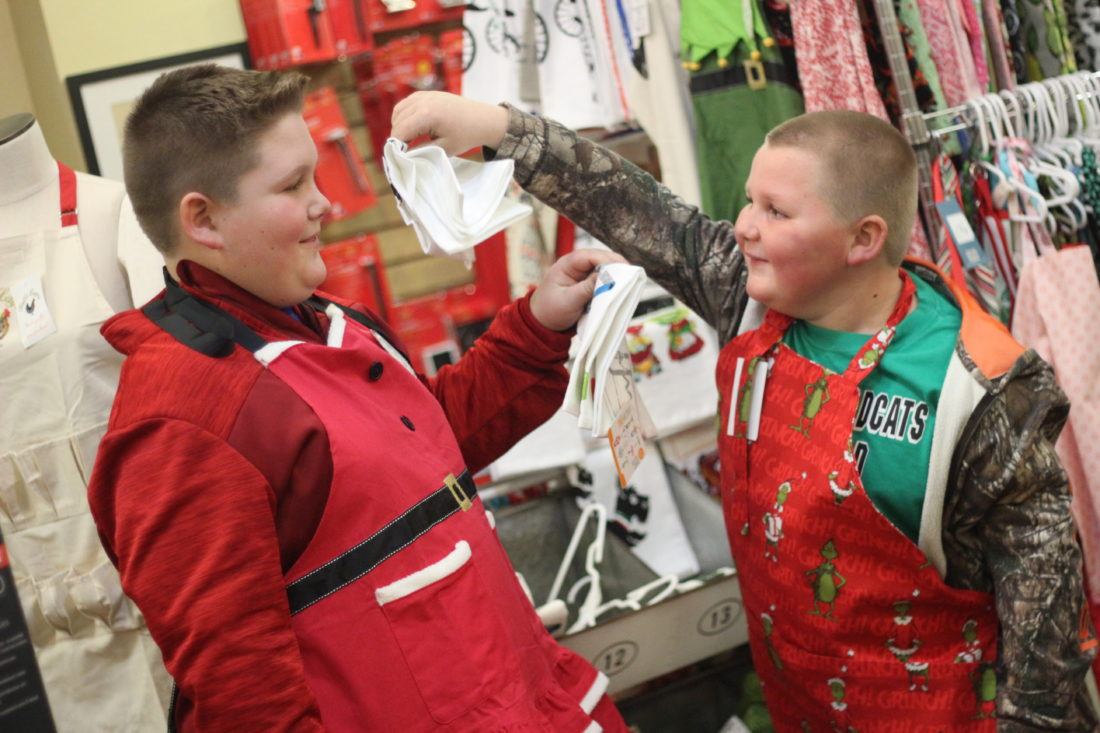 JANELLE PATTERSON   The Marietta Times Dalson Green, 11, left, and his brother Austin, 8, try on Christmas aprons at The Cook's Shop in Marietta Friday during Moonlight Madness.