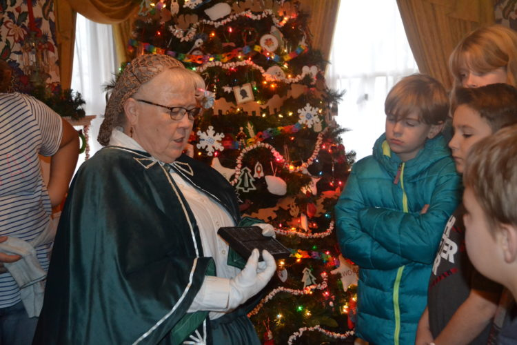 KATE YORK   The Marietta Times Washington County Historical Society member Mary Jo Hutchinson talks to a group of Harmar Elementary fifth graders Tuesday at the Henry Fearing House Museum. Behind them is the home's folk art tree.