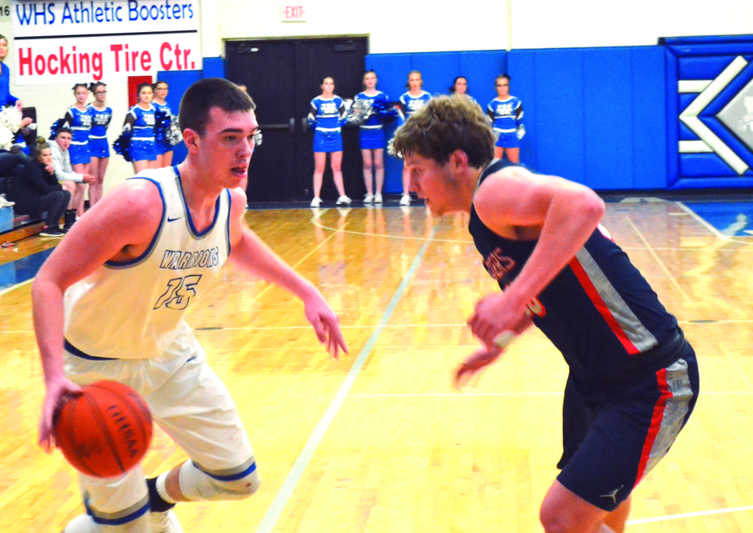 RON JOHNSTON The Marietta Times Warren's Josh Huffman, left, handles the ball as Morgan's Marty Sidwell defends during a high school boys basketball game Friday in Vincent.