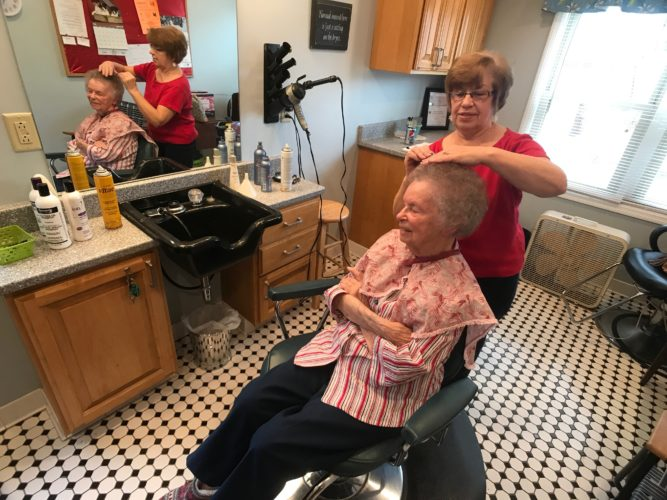 JANELLE PATTERSON   The Marietta Times Marlene Greene, right, picks through individual curls on Betty Rhodes, 95, a resident of the Woman's Home of Washington County, in Marietta Thursday.