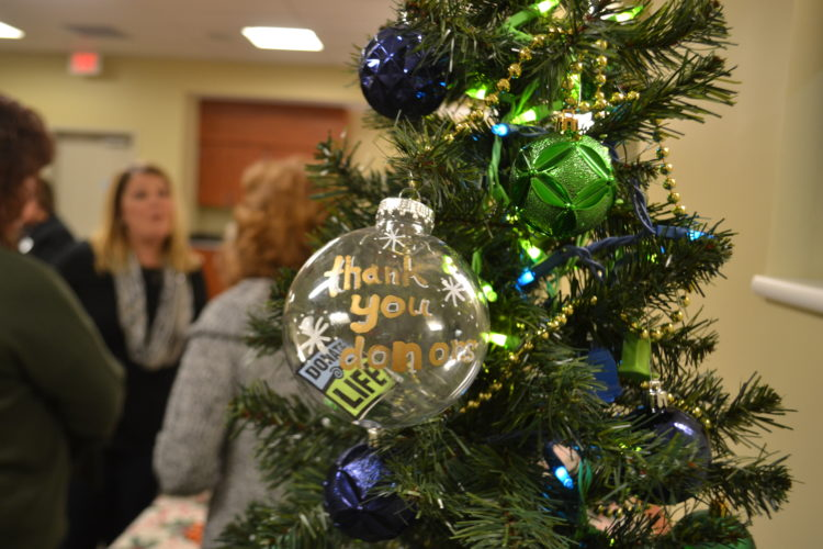 MICHAEL KELLY  The Marietta Times A hand-decorated ornament graces a Christmas tree while transplant recipients and the families of donors talk in the background at the annual Memorial Health System Gift of Life holiday gathering Thursday.