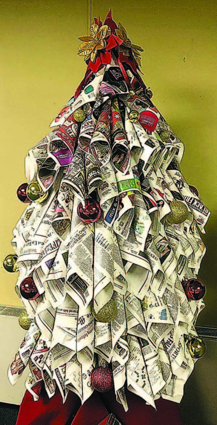 Newspaper tree Made out of coned newsprint and advertising inserts, The Marietta Times Christmas tree this year is held together with a cardboard center, staples and a bit of tape, then topped with two plastic poinsetta flowers and adorned with ornaments.