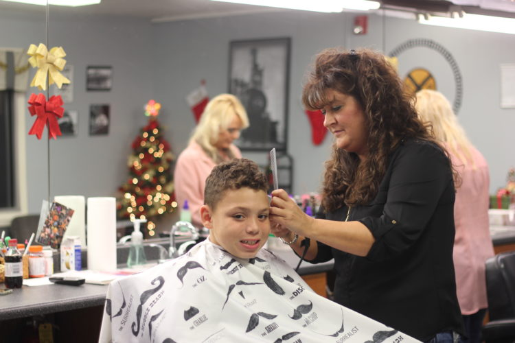 JANELLE PATTERSON   The Marietta Times Muskingum Barbershop owner Paula Bigley cuts the hair of Caiden Henderson, 8, of Lowell, Friday, in the Rathbone neighborhood of Marietta.