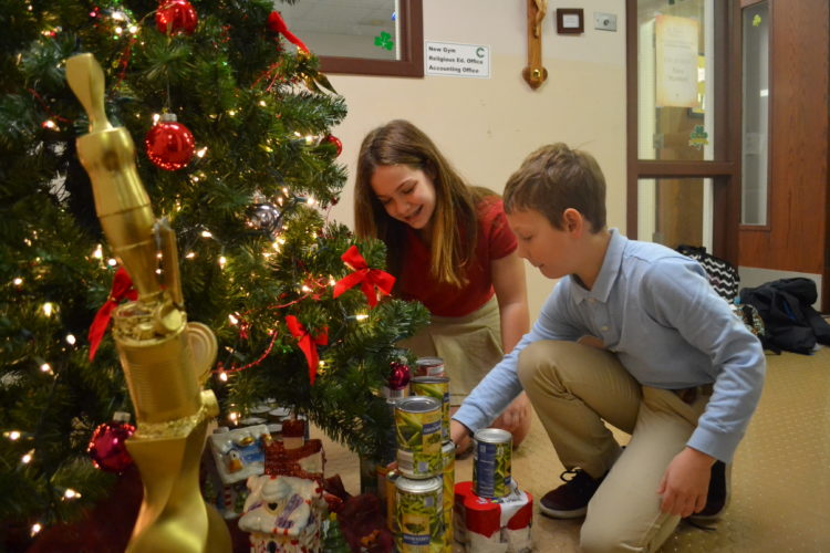 ERIN O'NEILL  The Marietta Times Lilly Westbrock, 12, and her brother, Luke, 9, place canned goods that have been collected by St. Mary Catholic School students under the Christmas tree. The first Food Fight competition not only fosters a spirited rivalry between St. Mary and St. John Central school — the winning school receives the trophy seen left — but ingrains in the students the need to provide service to the community.
