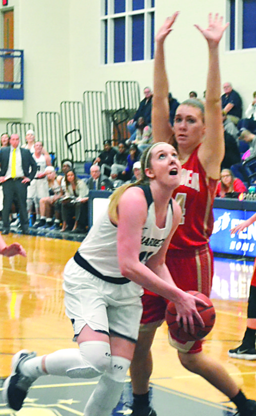 RON JOHNSTON The Marietta Times Marietta College's Alexis Enochs, left, drives to the basket during a college women's basketball game earlier this season at Ban Johnson Arena.