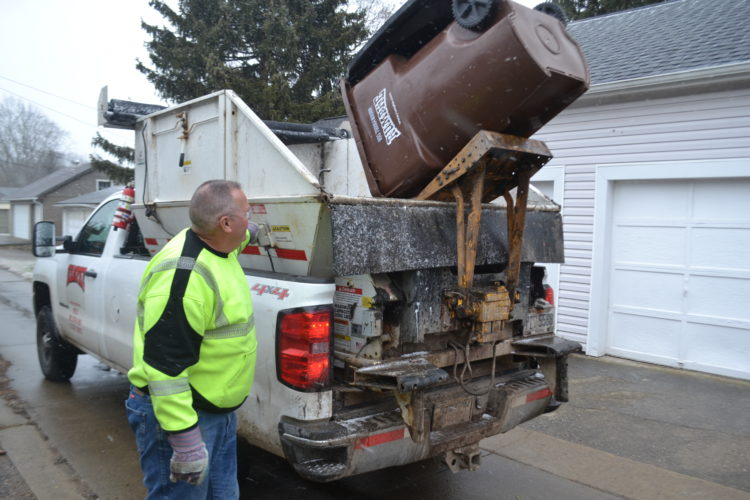 MICHAEL KELLY   The Marietta Times  Rumpke driver Jeff Dixon operates a lift to tip the contents of a residential trash bin into the hopper on the back of his truck in an alley near Seventh and Montgomery streets in Marietta,